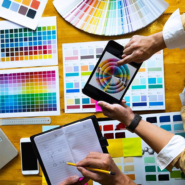 A person holding a tablet over a range of colour selection tools